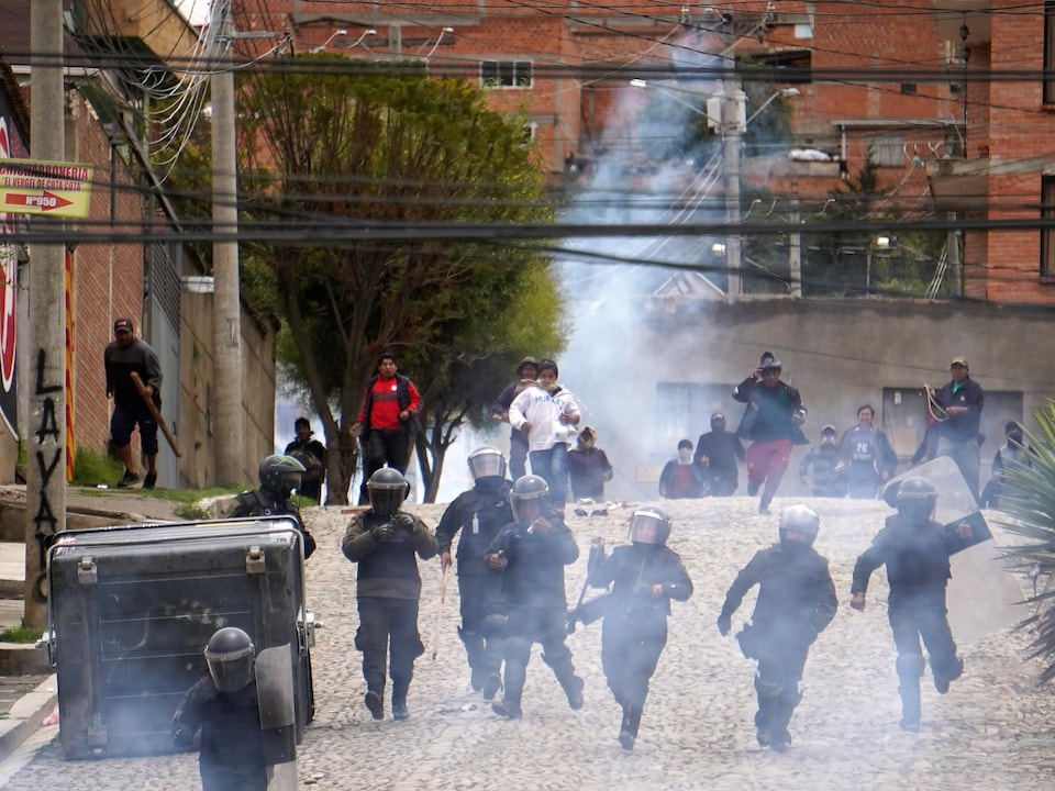 Des policiers et des manifestants courent dans la rue.