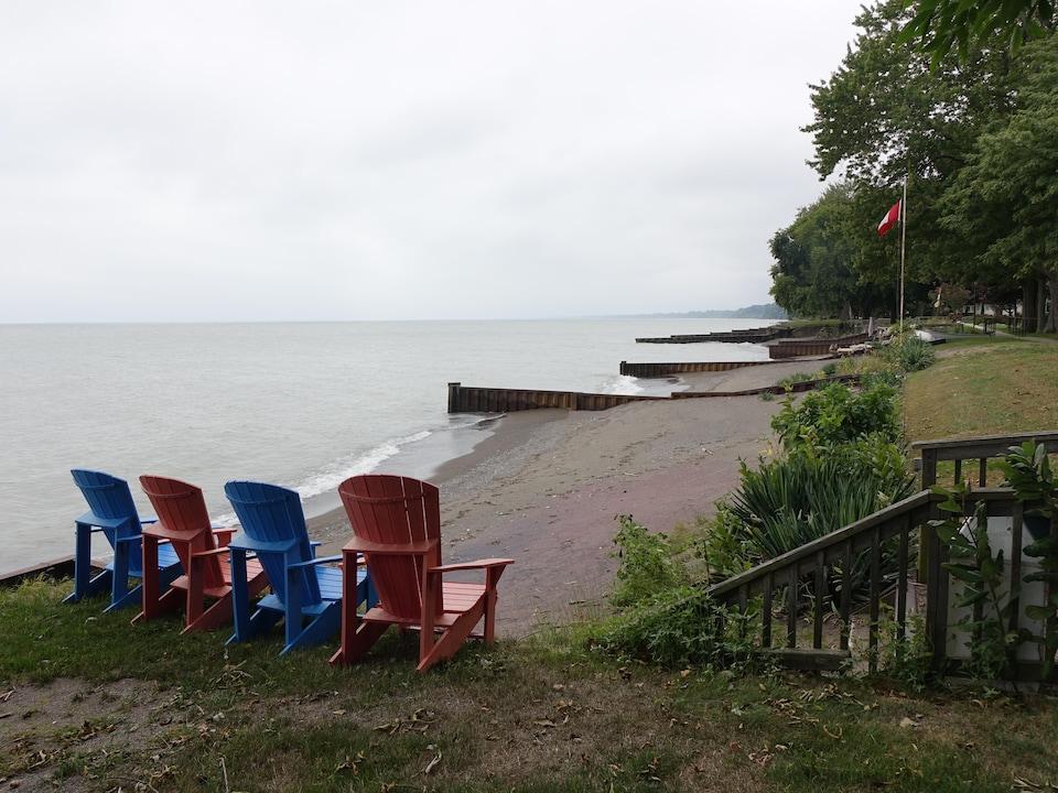 On voit des chaises alignées près d'une plage du lac Érié.