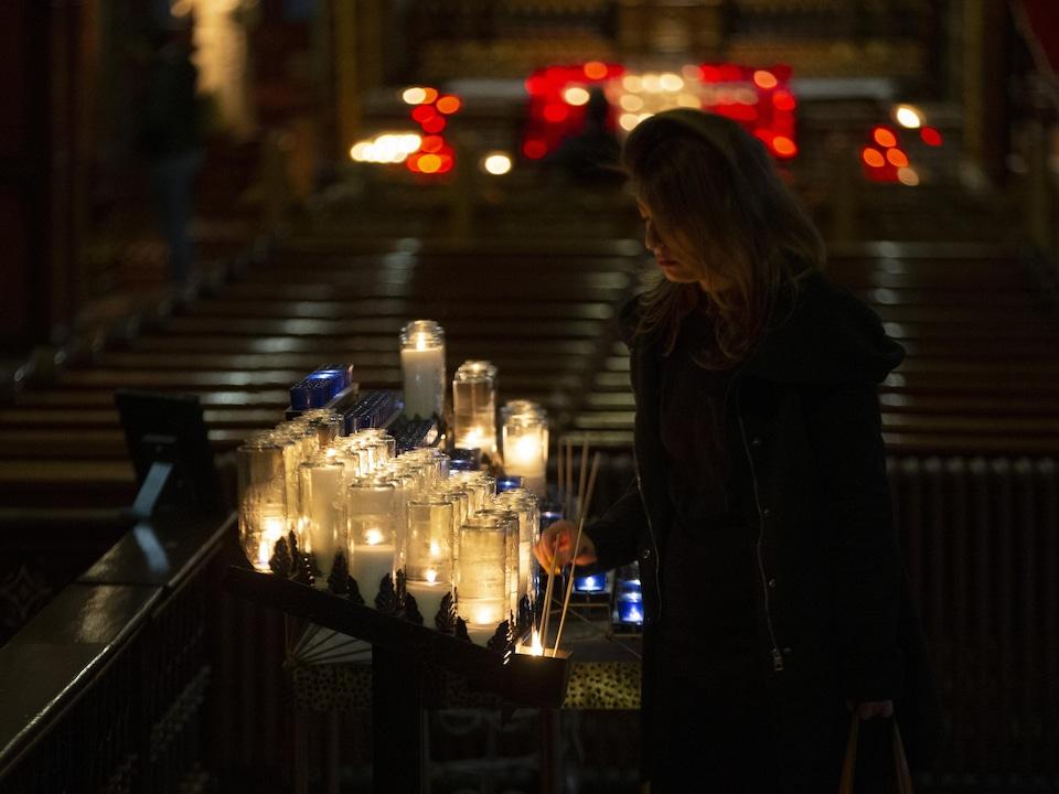Une femme allume un lampion.