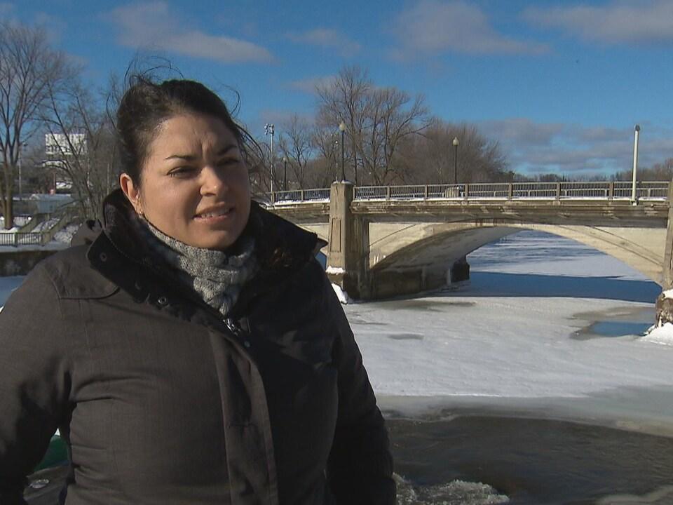 On voit Mme Laniel, debout, qui parle à la caméra. Derrière elle, on voit un pont qui enjambe un cours d'eau gelé.
