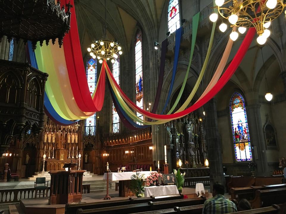 Deux banderoles aux couleurs de l'arc-en-ciel sont suspendues du chandelier central jusqu'aux balustrades le long de la pièce.