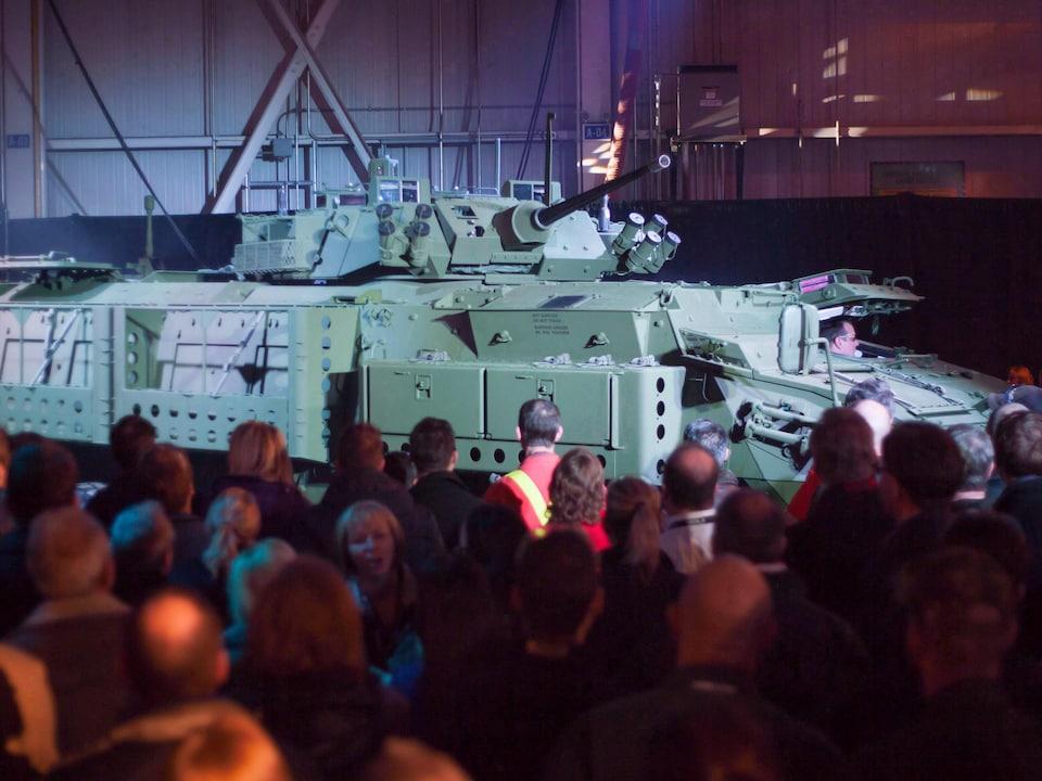 Des gens assistent à la présentation d'un véhicule LAV lors d'une conférence de presse à London, en Ontario.