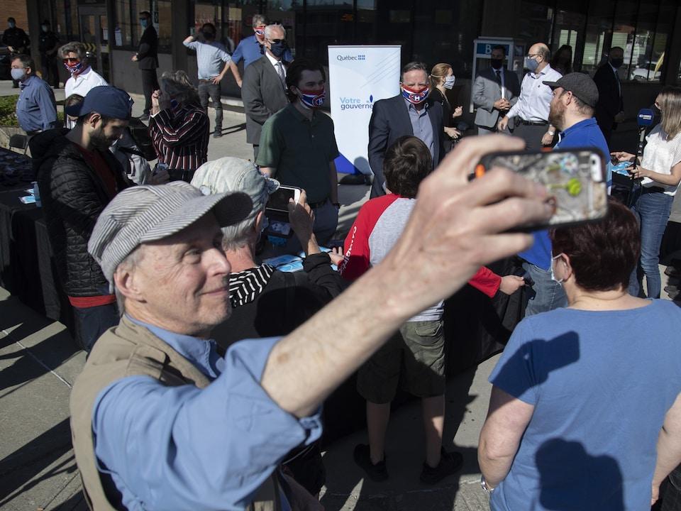 Un homme se prend en photo au milieu de la foule avec, en arrière-plan, le premier ministre Legault, Jonathan Drouin et Marc Bergevin.
