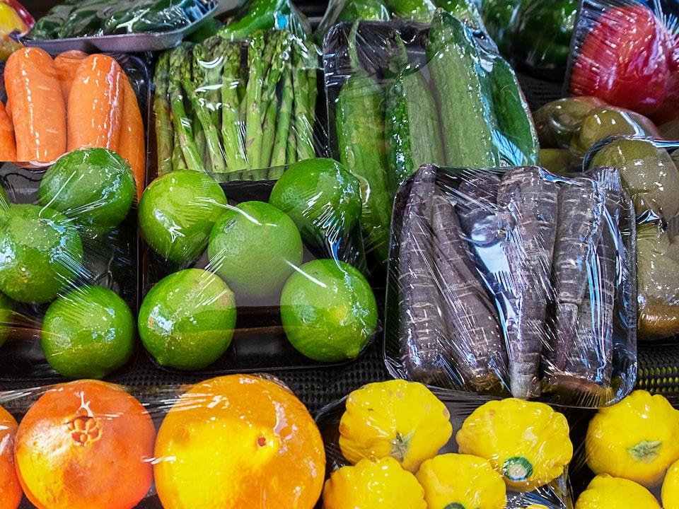 Des fruits et légumes enveloppés de plastique.
