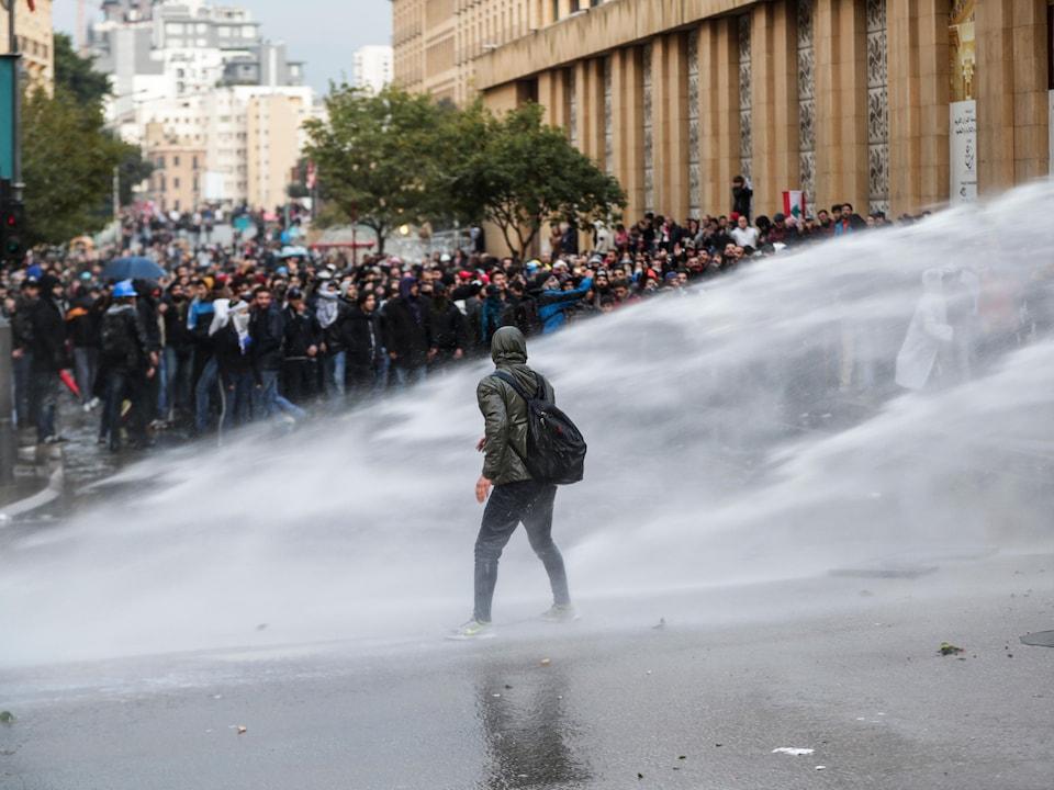 Un manifestant marche à travers des jets d'eau projetés par les policiers sur une foule devant le parlement.