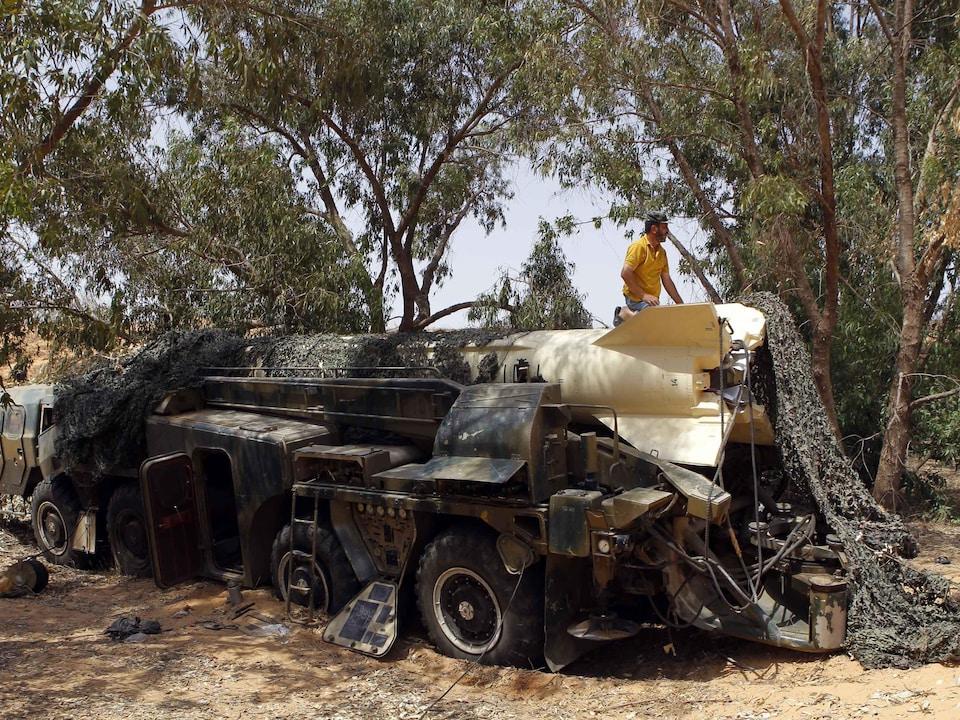 Un homme est agenouillé sur un missile transporté par un camion dans la forêt.