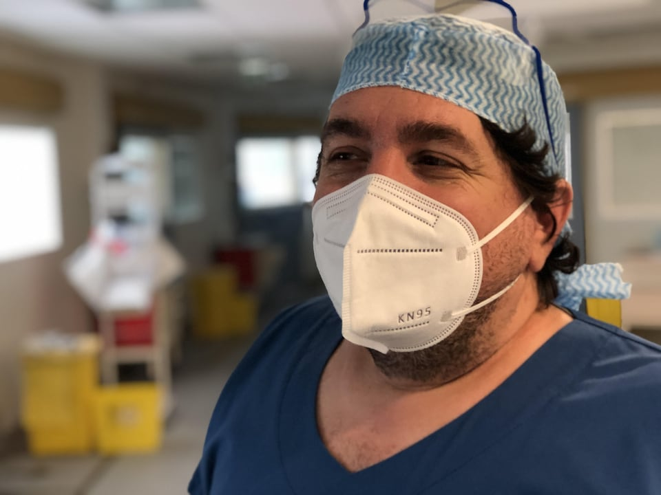 Portrait de Lionel Velly qui porte un masque N95 dans un corridor d'urgence.