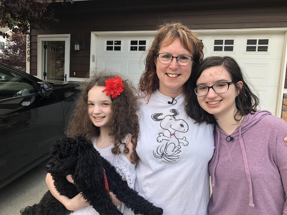 Une mère et ses deux filles se tiennent debout devant leur maison.