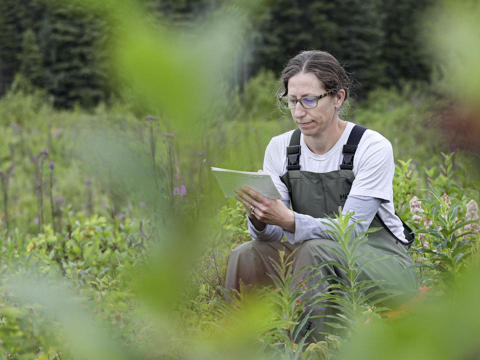 Une femme accroupie dans la forêt prend des notes.