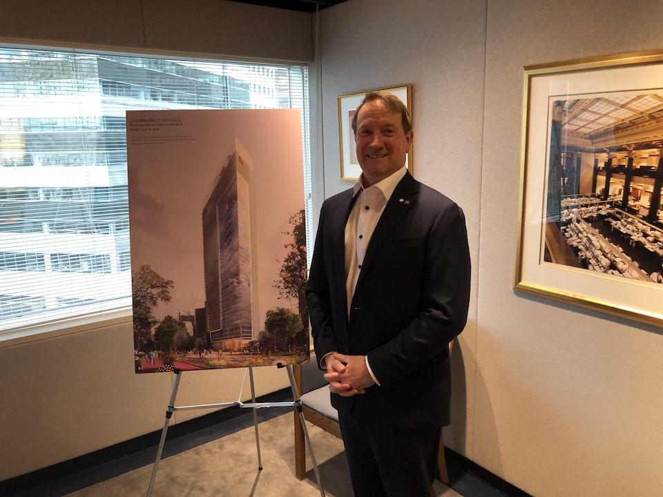 On voit M. Vachon, debout, qui sourit à la caméra. Il est dans un bureau devant une fenêtre et une représentation du nouvel édifice de la Banque Nationale.