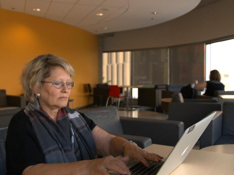 On voit Mme Vandelac qui travaille à l'ordinateur.
