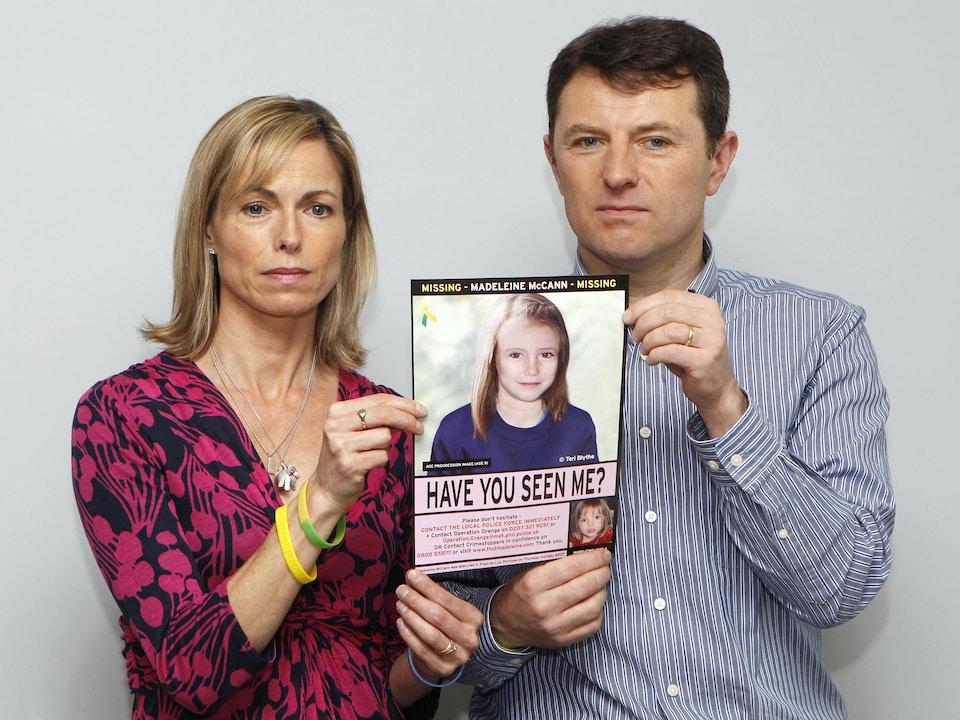 Gerry et Kate tiennent ensemble une photo de leur fille avec les doigts.