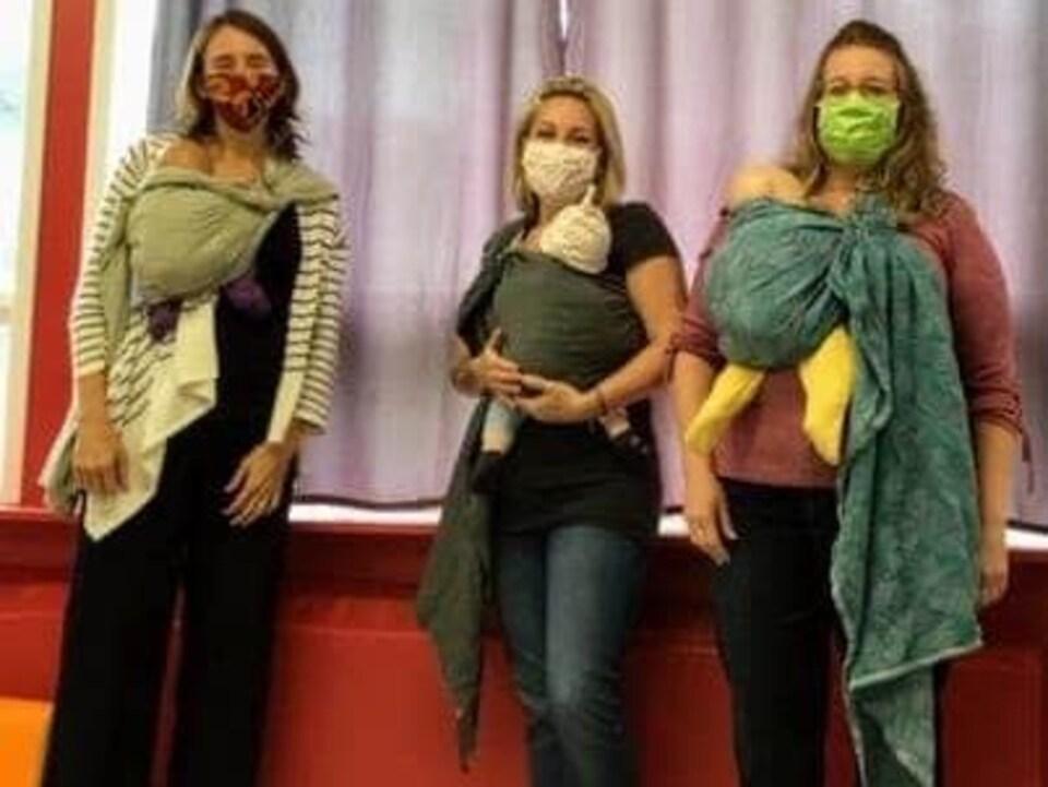 Trois femmes qui portent un masque et qu portent leur bébé dans un drap enroulé autour d'elles.