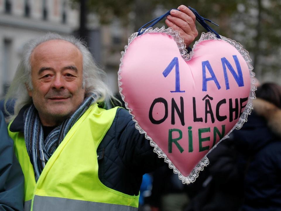 Un manifestant tenant un coussin en forme de coeur où on peut lire « 1 an on lâche rien ».