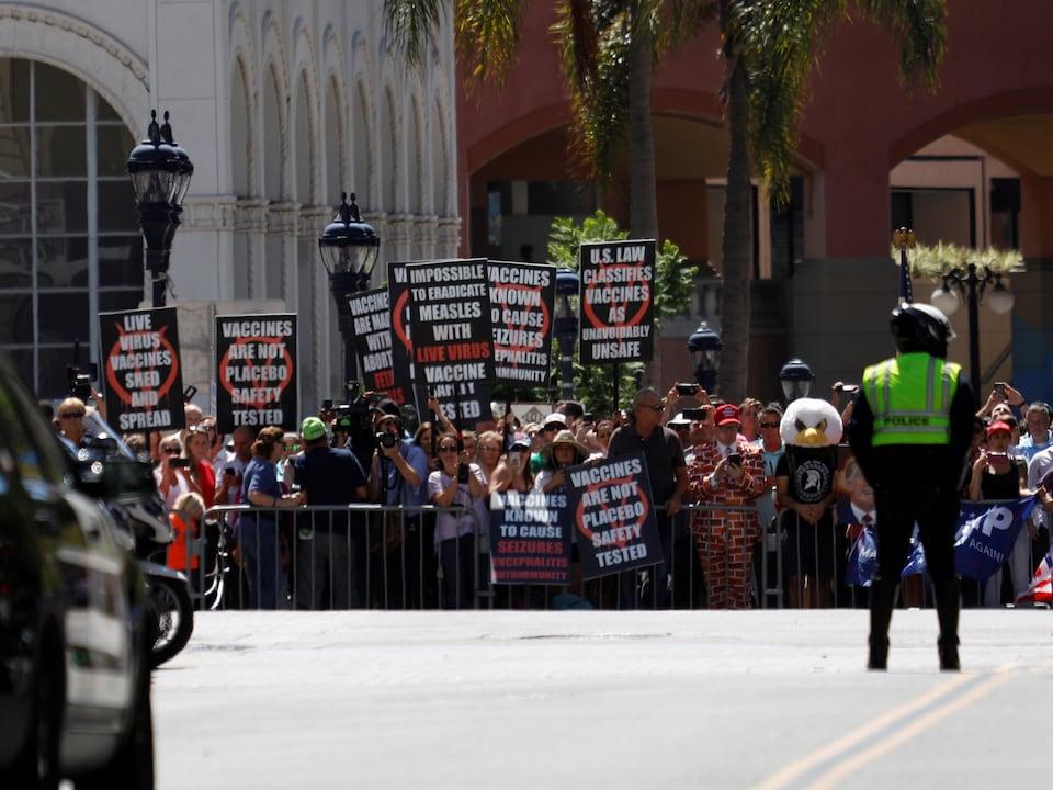 Un policier se tient devant une foule de manifestants, dont plusieurs tiennent des pancartes contre la vaccination.