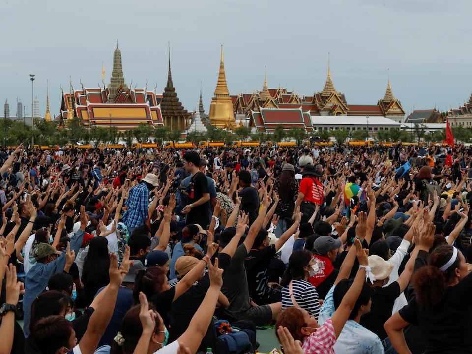 Des manifestants font le salut à trois doigts avec des temples en arrière.
