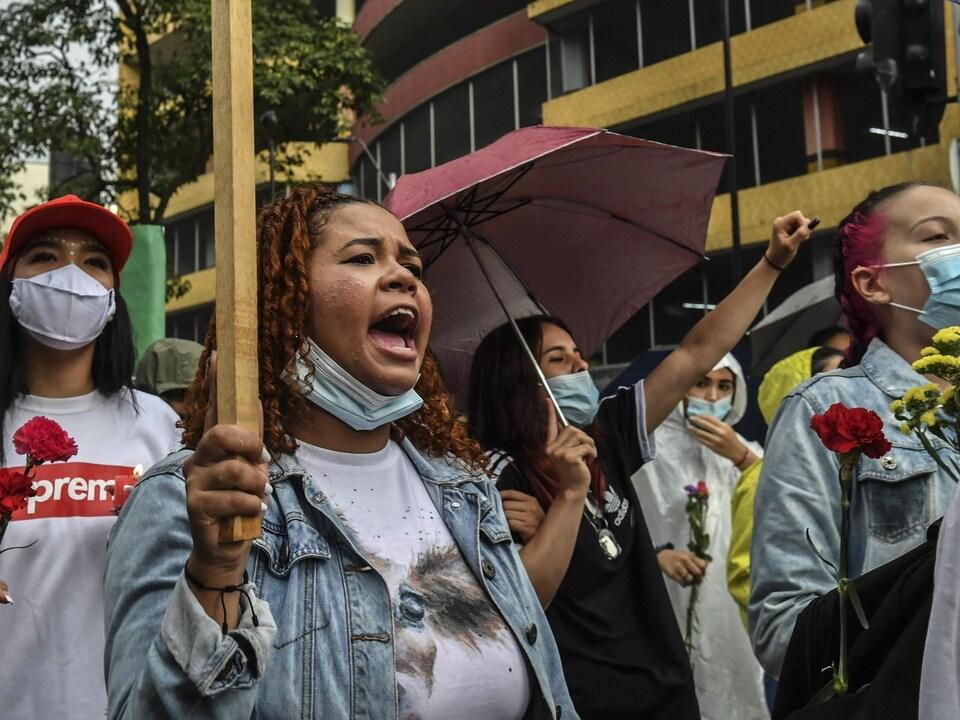 Des femmes, dont certaines ont le visage couvert d'un masque sanitaire, marchent en tenant des oeillets.