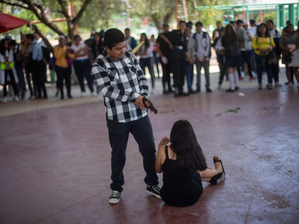 Un homme menace une femme avec un revolver. En arrière-plan, des spectateurs.