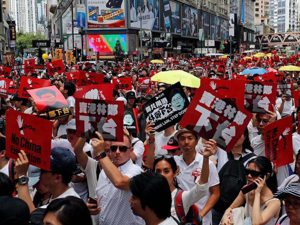 Foule de manifestants brandissant de petites pancartes.