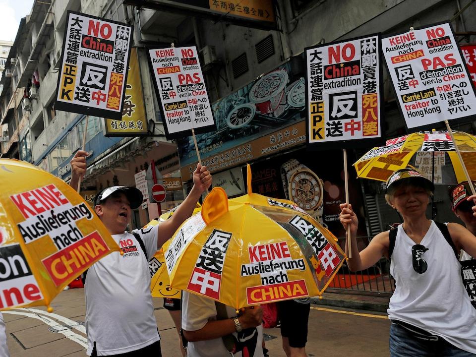 Quelques manifestants tiennent des parapluies jaunes et des pancartes.