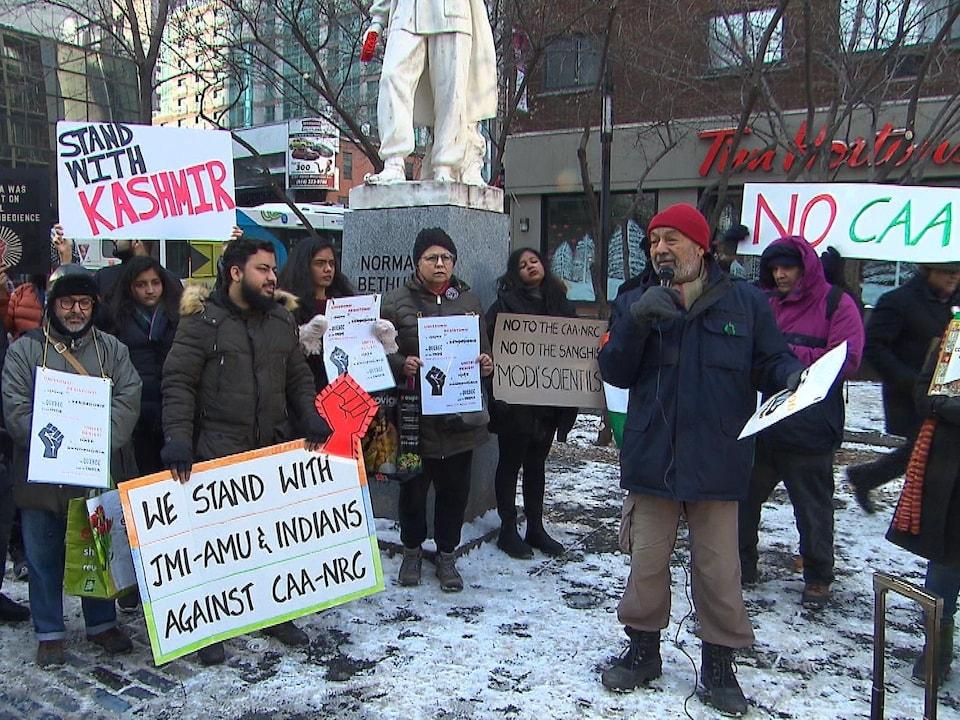 Des personnes brandissent des pancartes près d'une statue à Montréal en hiver.