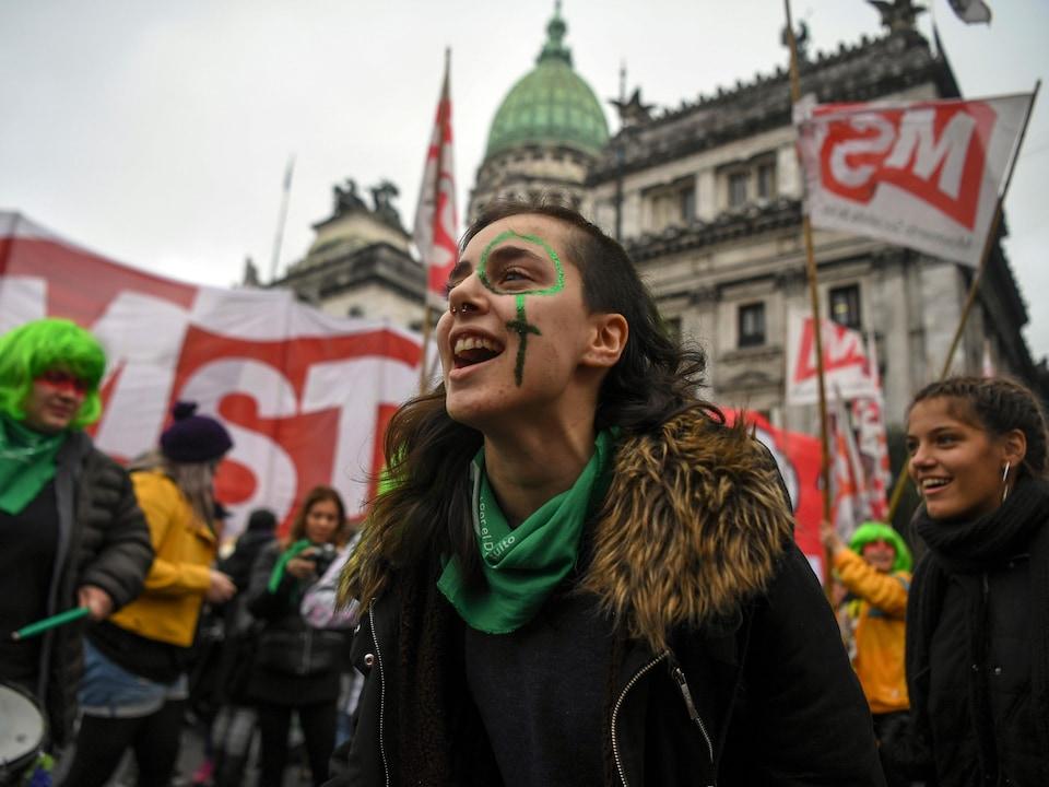 Des personnes souriant et portant des foulards ou des perruques vertes sont photographiées devant un grand bâtiment. Certaines d'entre elles tiennent des banderoles et d'autres jouent du tambour.