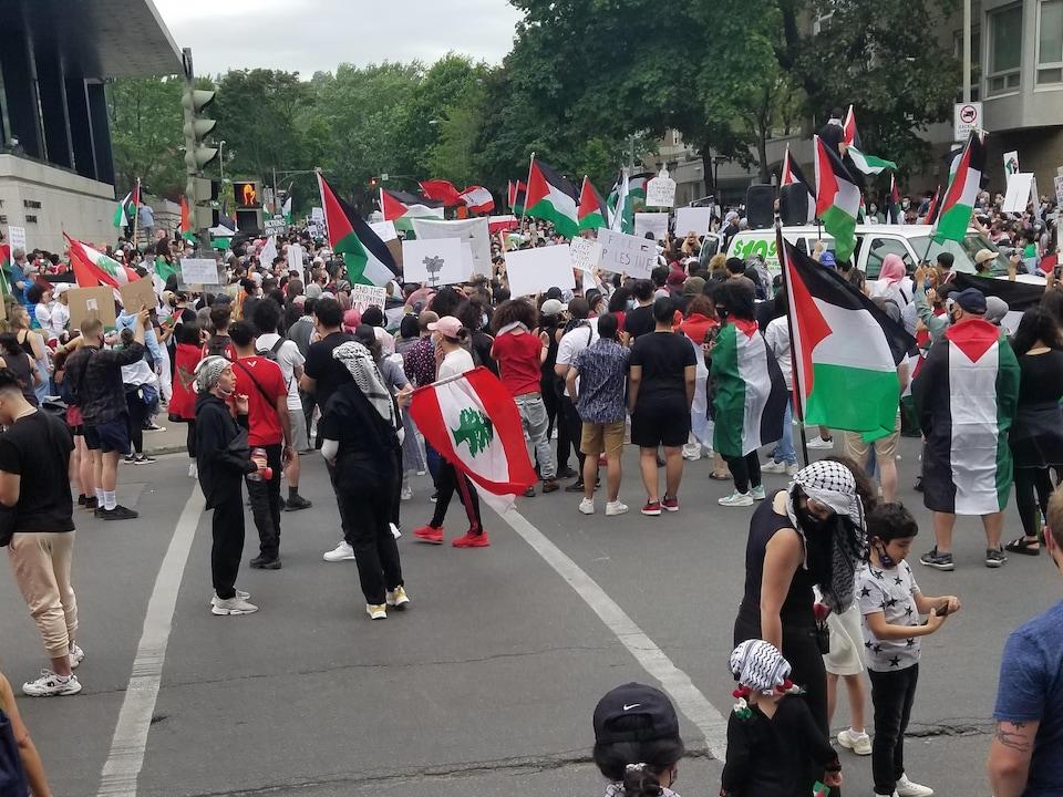 Des personnes occupent une rue et tiennent des drapeaux et des pancartes.