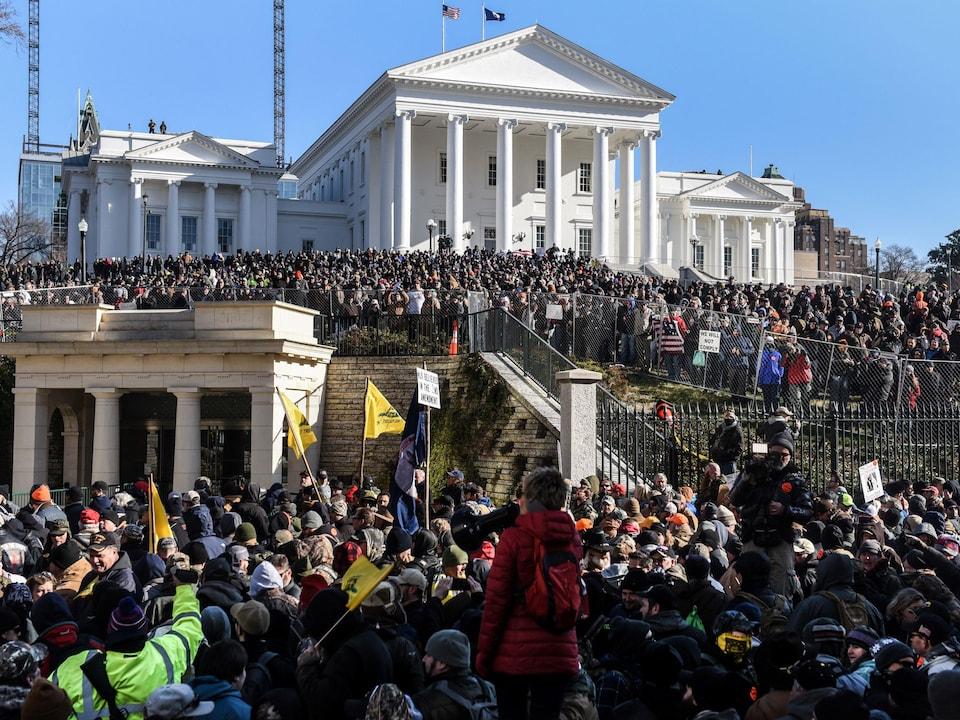 Une foule se trouve devant un large édifice sur lequel flotte notamment le drapeau américain. Certaines personnes dans cette foule tiennent des drapeaux ou des pancartes.