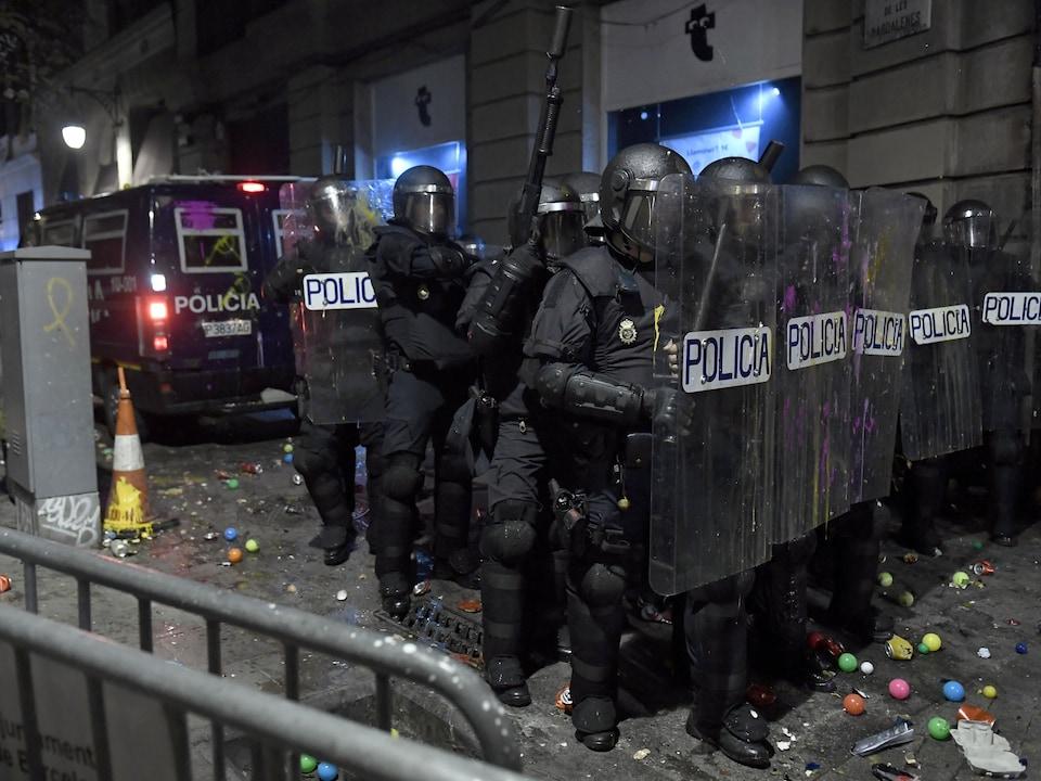 Des policiers derrière leurs boucliers antiémeutes se tiennent en ligne, ont reçu différents projectiles.
