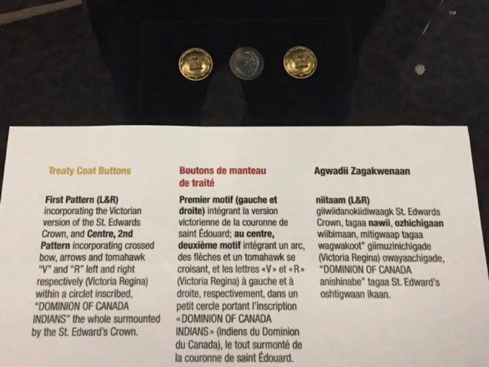Trois boutons anciens en métal avec des explications historiques.