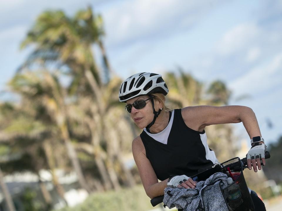 Une femme à vélo, portant un casque.
