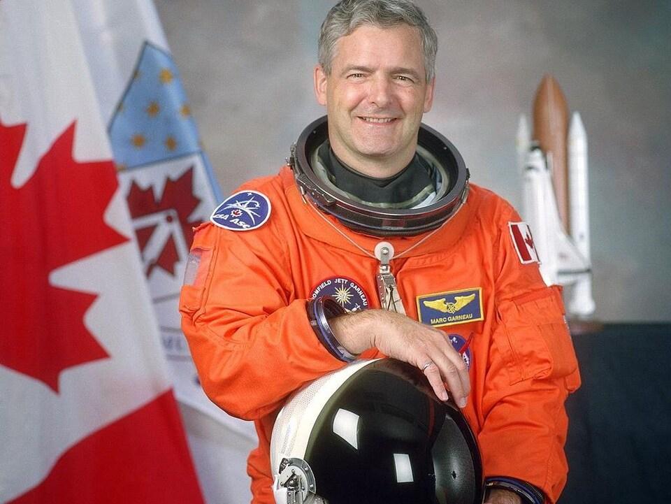 L'astronaute Marc Garneau devant le drapeau canadien.