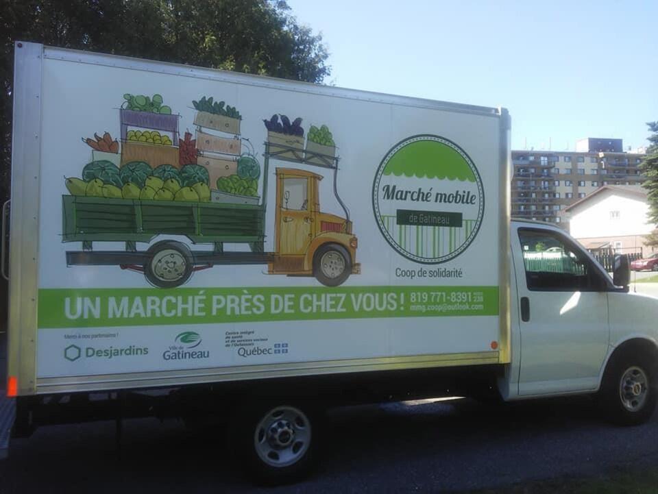 """Un camion arborant un logo et une mention disant """"Un marché près de chez vous!"""""""