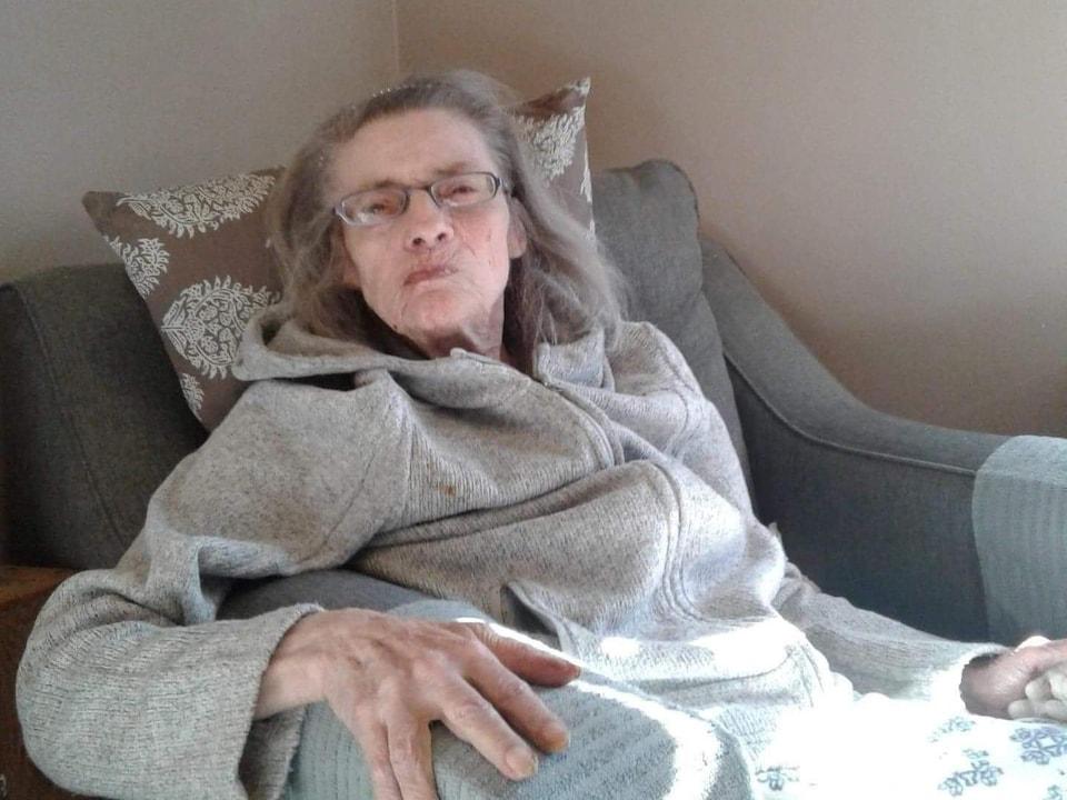 La dame assise sur un fauteuil.