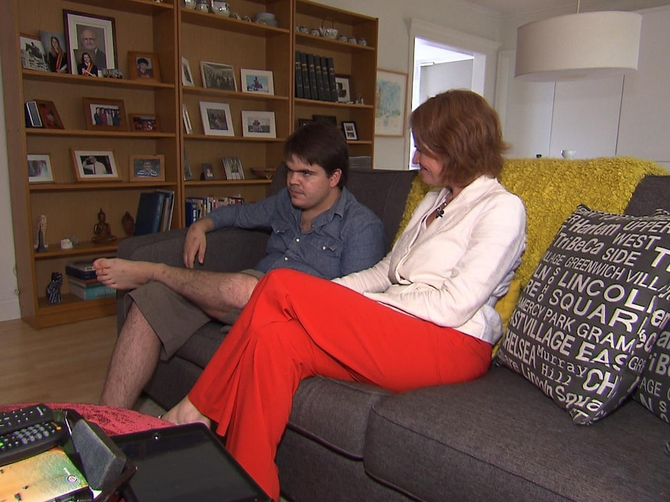 La mère et son fils sont assis sur le divan.