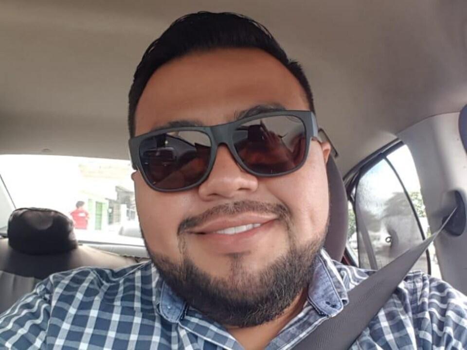 Mario Luis Castillo souriant dans une voiture.