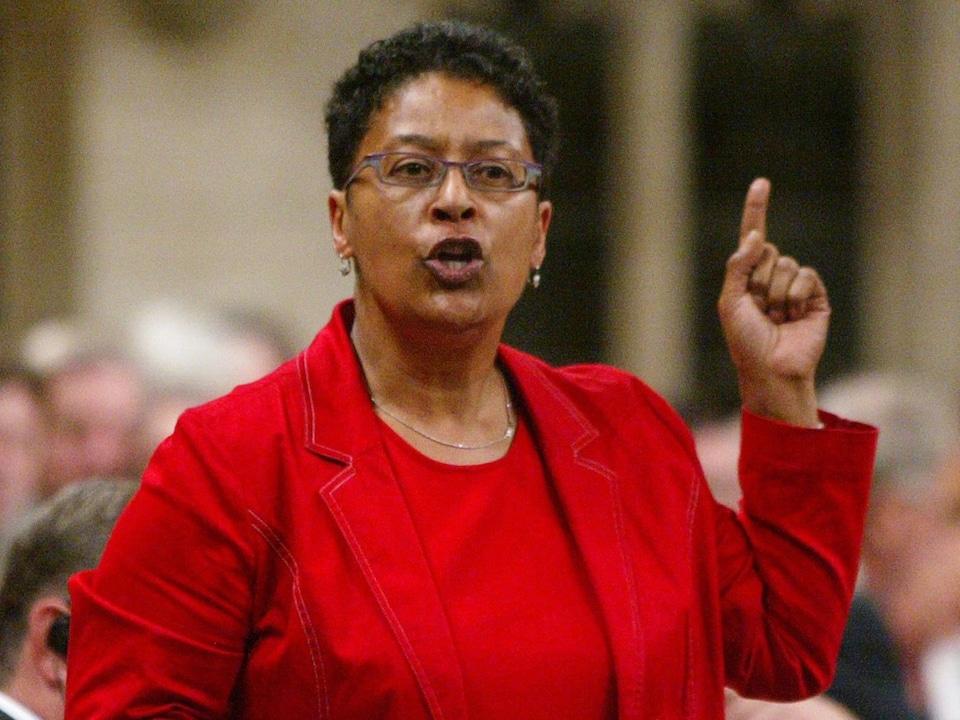 Marlène Jennings parle devant une assemblée en levant le doigt.