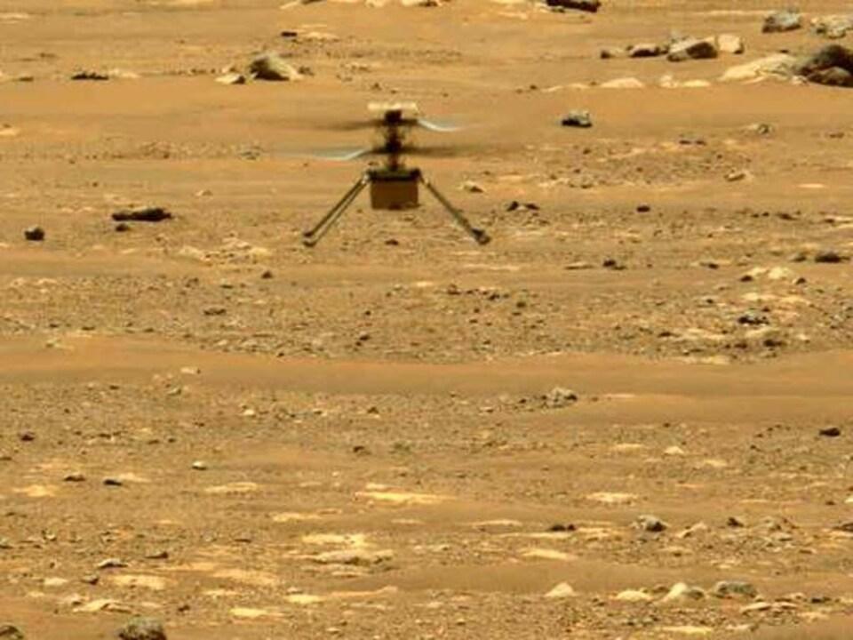 L'hélicoptère vole au-dessus de la surface martienne.