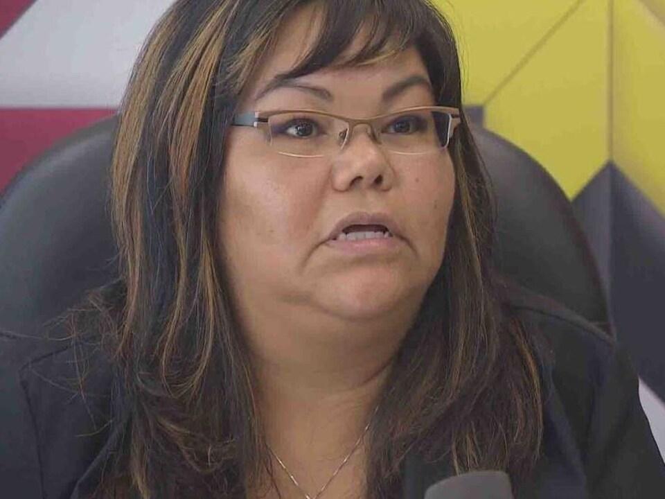 Une femme portant des lunettes, avec un mur coloré derrière elle.