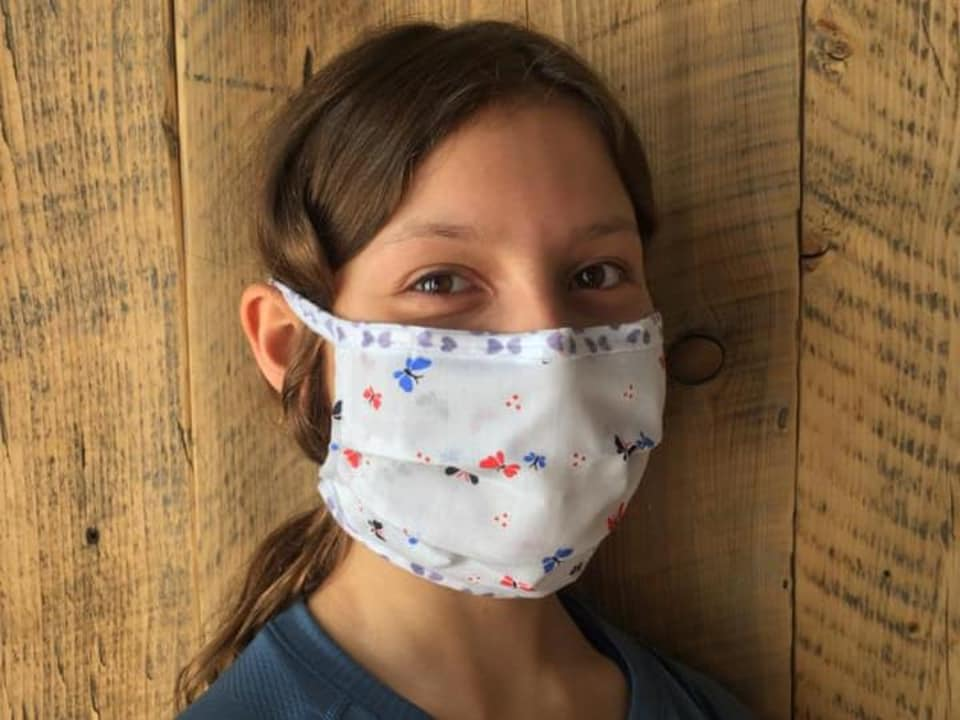 Une jeune fille porte un masque en tissus.