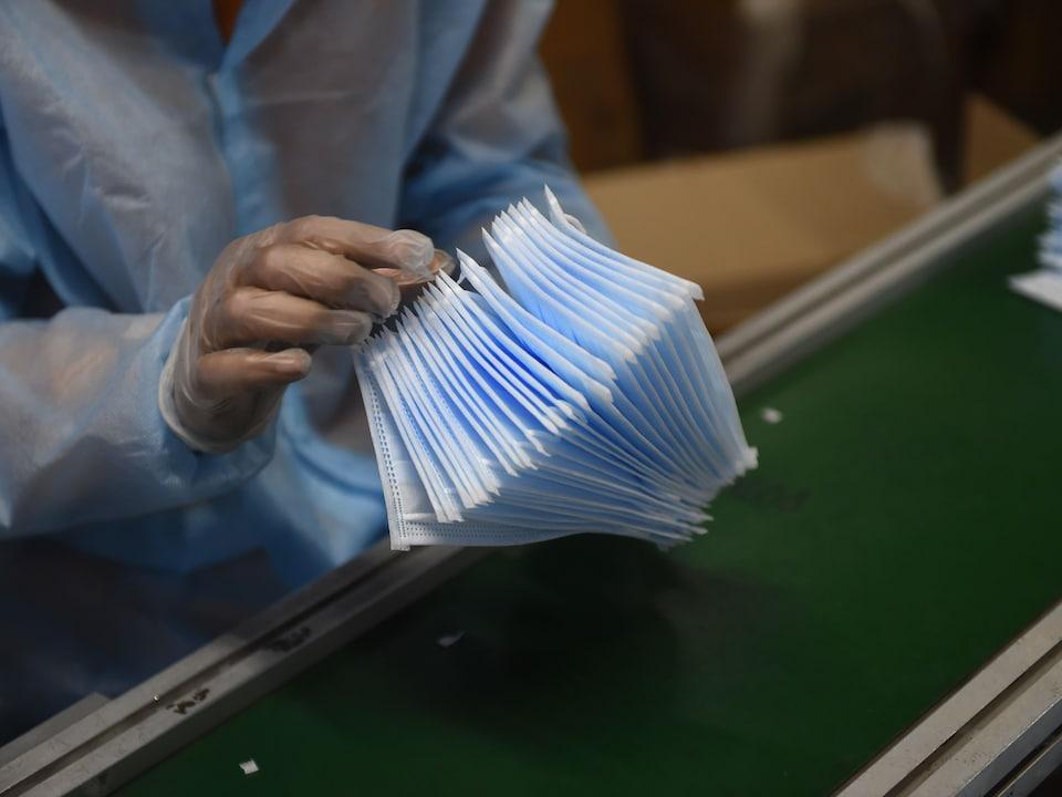 Une employée de manufacture qui porte des vêtements de protection tient une pile de masques chirurgicaux.