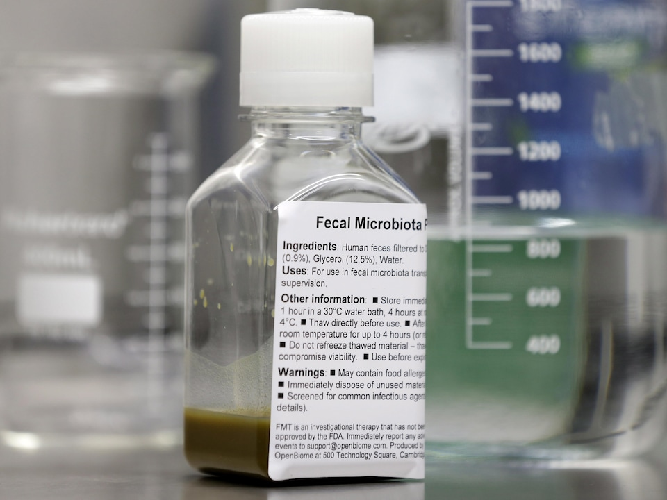 On voit une bouteille transparente remplie au quart d'une solution brune, posée sur une surface. En arrière-plan, des contenants gradués de laboratoire.