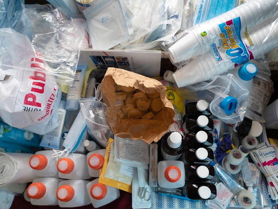 On voit les bouteilles de médicaments et les autres fournitures médicales rassemblées dans le salon du couple Desjardins.
