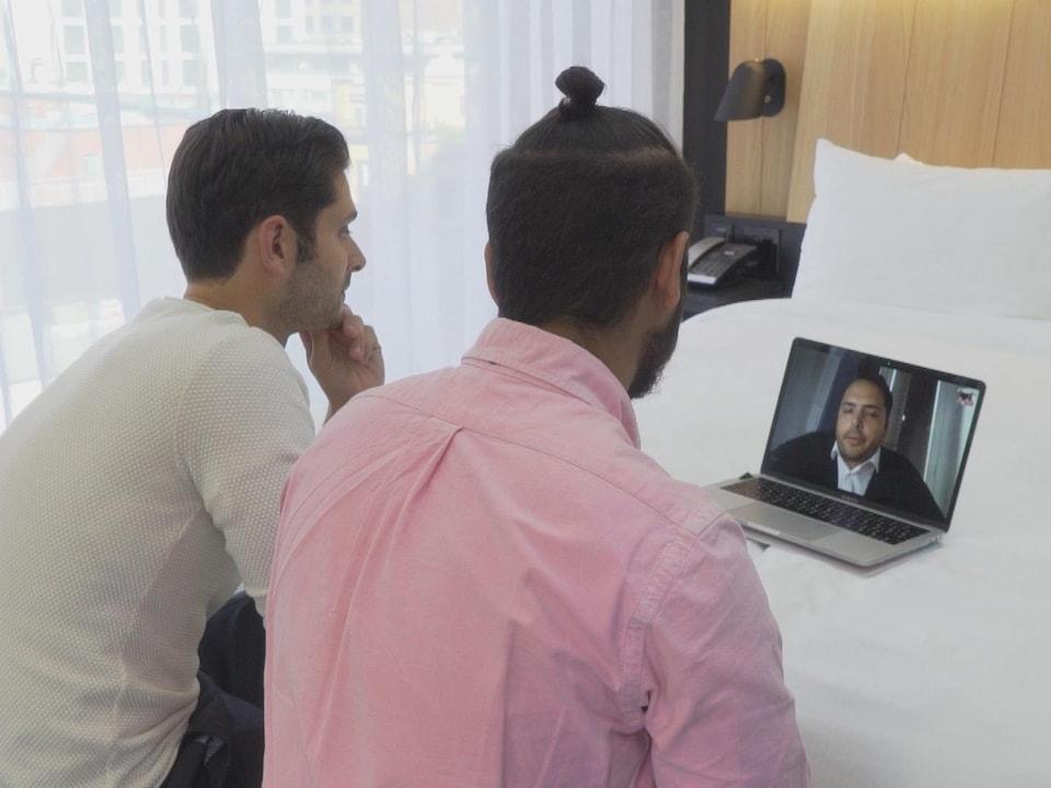 On voit Mauricio et Mario Di Bartolomeo, dans une chambre, qui discutent par vidéoconférence avec leur frère Daniel.