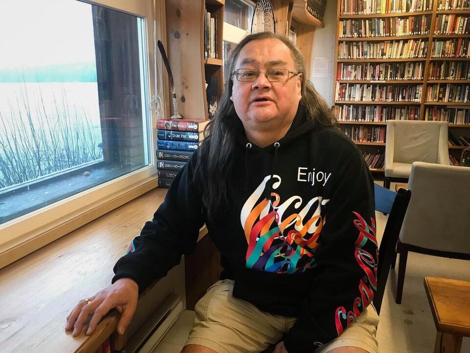 Un homme assis dans une bibliothèque.