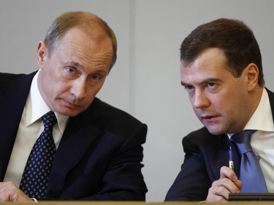 Vladimir Poutine et Dimitri Medvedev discutent, penchés l'un vers l'autre.