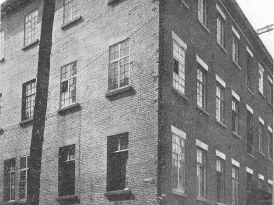 Un immeuble en briques sur une photo noir et blanc