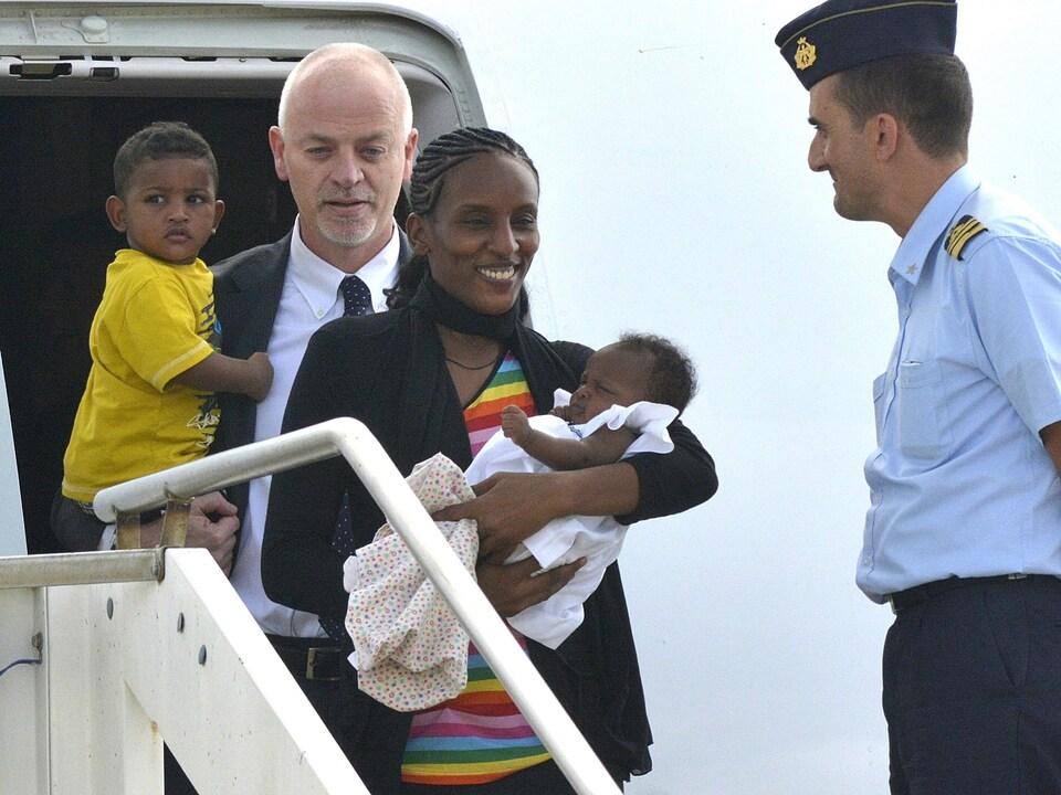 La jeune femme souriante descend de l'avion avec son bébé dans les bras.