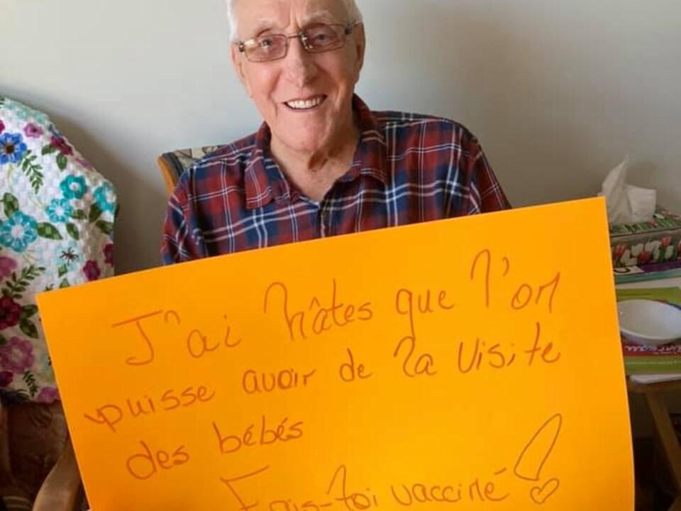 Normand Gionet tient une affiche: J'ai hâte qu'on puisse avoir la visite de bébés, fais-toi vacciner.