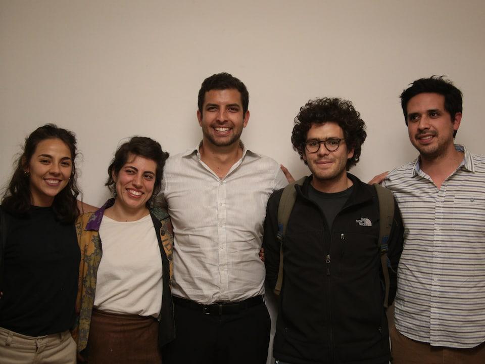 Cinq jeunes posent sur un fond blanc.